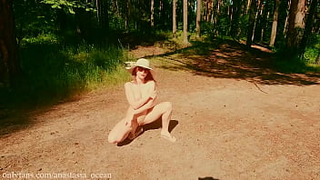 A nudist girl walks in forest near the beach among dressed people. (Emerald Ocean)